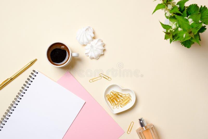 Vlak leg vrouwelijke toebehoren, lege document blocnote, koffiekop, heemst, parfumfles, bloemen op pastelkleurenbeige royalty-vrije stock afbeeldingen