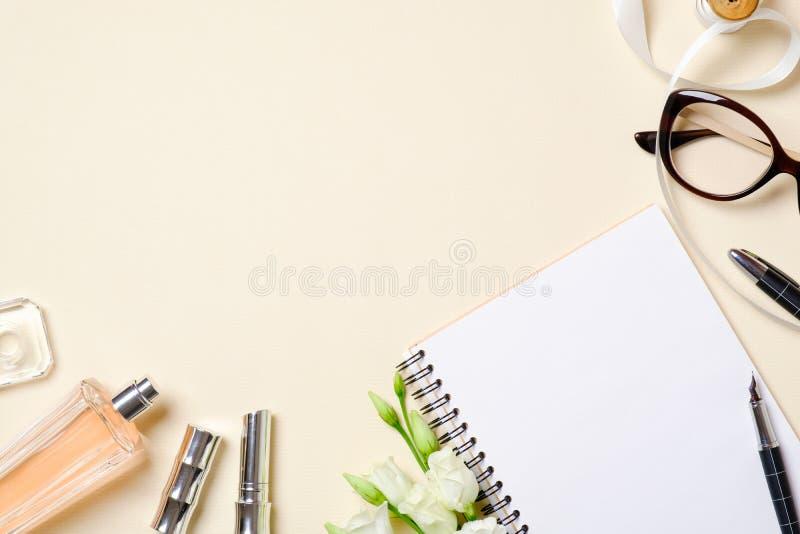 Vlak leg vrouwelijke toebehoren, schoonheidsschoonheidsmiddel, glazen, rozenbloemen op beige pastelkleurenachtergrond Het hoogste stock foto's