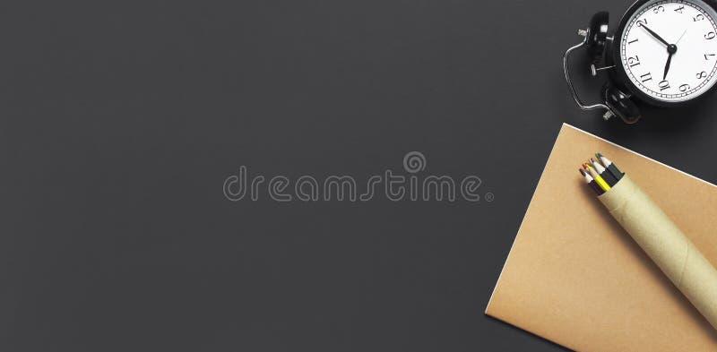 Vlak leg zwarte wekker, de agenda van het oefenboeknotitieboekje, kleurenpotloden op de grijze donkere ruimte van het achtergrond stock afbeeldingen