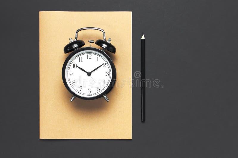 Vlak leg zwarte wekker, de agenda van het oefenboeknotitieboekje, potlood op de grijze donkere ruimte van het achtergrond hoogste stock foto's