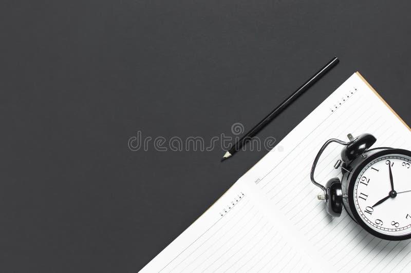 Vlak leg zwarte wekker, schone open notitieboekjeagenda, potlood op de grijze donkere ruimte van het achtergrond hoogste meningse royalty-vrije stock afbeelding