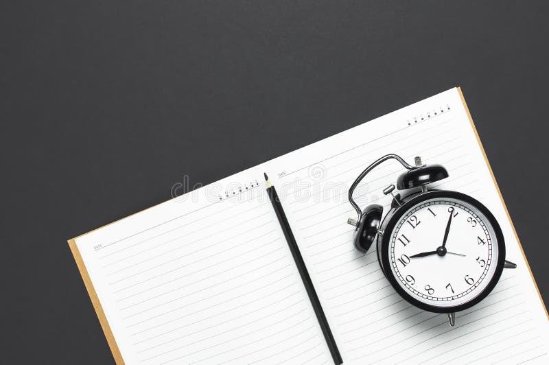 Vlak leg zwarte wekker, schone open notitieboekjeagenda, potlood op de grijze donkere ruimte van het achtergrond hoogste meningse stock foto