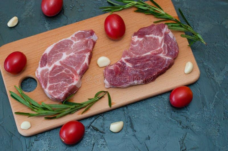 Vlak lekken, rauw vlees, twee varkenssteak met tomaten, knoflook en rozemarijn op een houten afsnijplaat royalty-vrije stock afbeelding