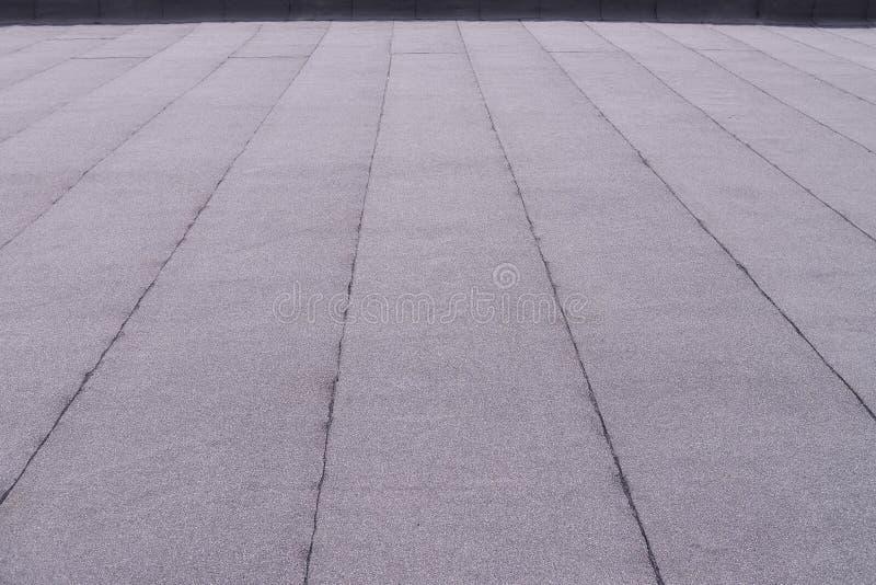 Vlak opgedoken dakdeklaag Verwarmend en smeltend bitumendakwerk gevoeld patroon als achtergrond stock afbeeldingen
