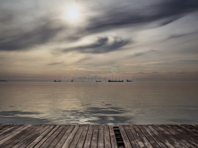 Vlak v??r het onweer - grote schepen op de horizon die - door het overzees lopen royalty-vrije stock afbeeldingen