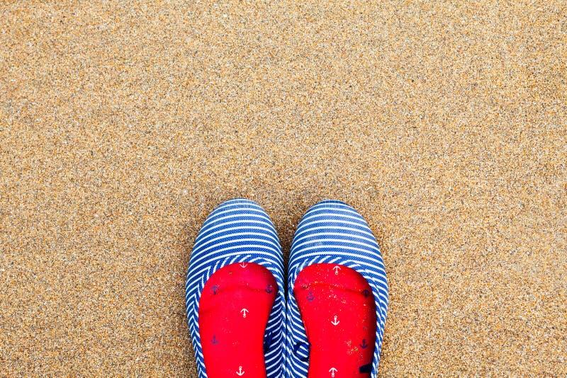 Vlakke de zomerschoenen van vrouwen, tegen een zandachtergrond stock afbeeldingen