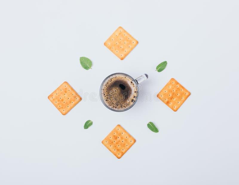 Vlakke lay-out van crackers, groene bladeren en kop van zwarte koffie in centrum op witte achtergrond De hoogste samenstelling va royalty-vrije stock foto