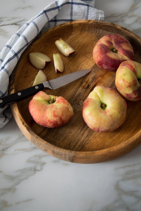 Vlakke perziken met mes en handdoek in houten kom op marmeren lijst stock afbeelding