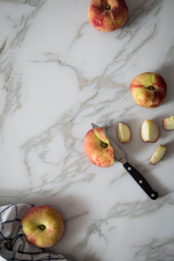 Vlakke perziken met mes en handdoek op marmeren lijst stock afbeelding