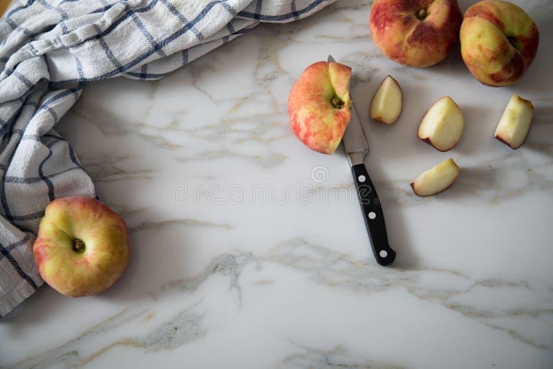 Vlakke perziken met mes en handdoek op marmeren lijst royalty-vrije stock foto