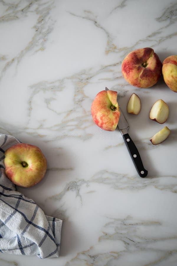 Vlakke perziken met mes en handdoek op marmeren lijst stock foto