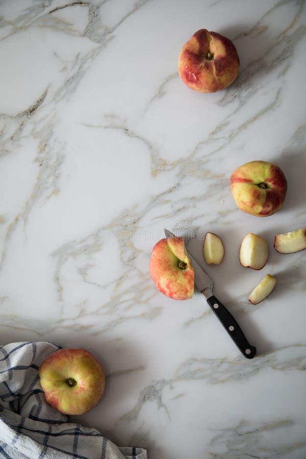 Vlakke perziken met mes en handdoek op marmeren lijst royalty-vrije stock afbeelding