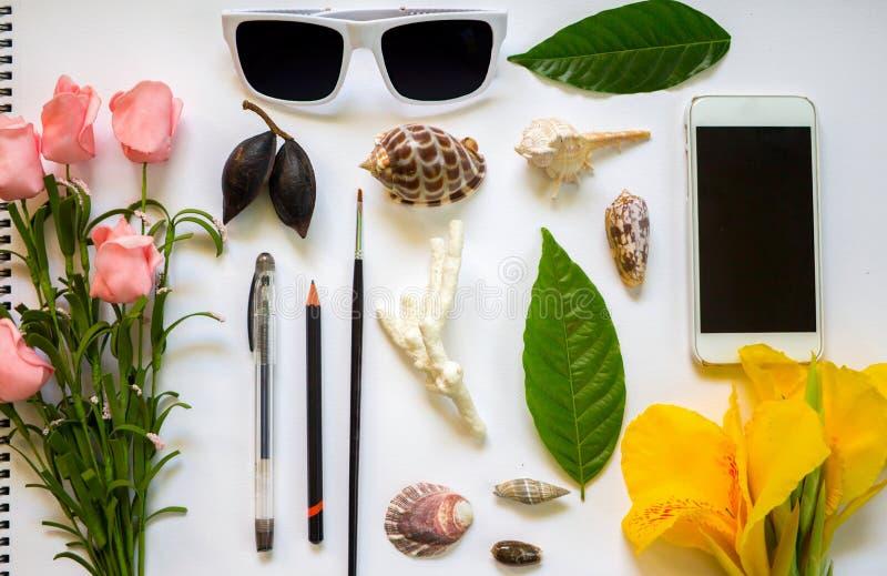 Vlakke samenstelling op witte blocnote Tropische bloemen en bladeren Overzeese shell kunst levering royalty-vrije stock afbeelding