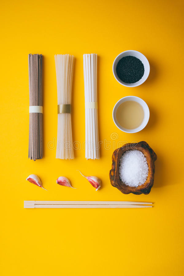 Vlakke stijl, Aziatische rijstnoedels, soba en udon met een kom zwarte sesam en rijstazijn royalty-vrije stock foto
