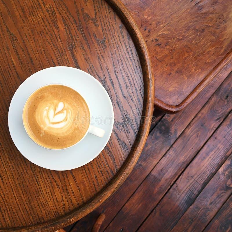 Vlakke witte koffie op de retro lijst stock afbeeldingen