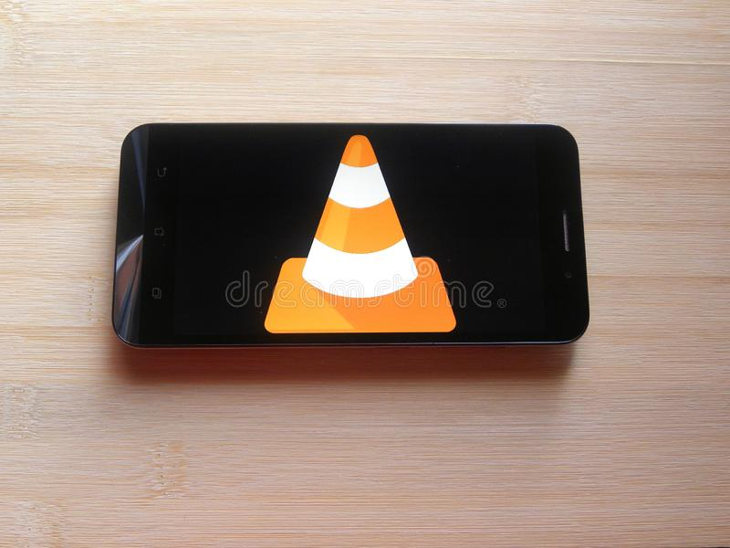 VLC media player app. On smartphone kept on wooden table royalty free stock image