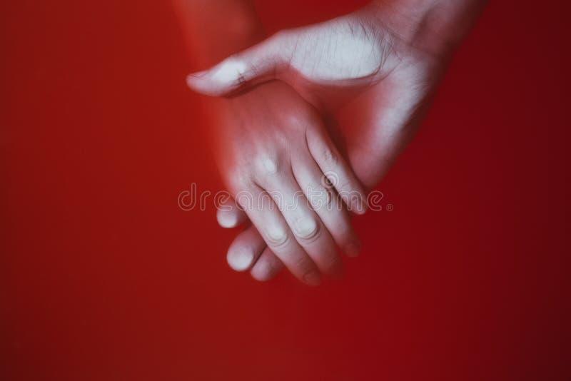 Vlecht van de handen van een man en een vrouw in rood bloedig water, conceptendrama in verhoudingen en verraad royalty-vrije stock foto's