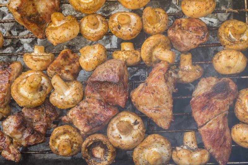 Vlees het koken met gebiedspaddestoelen openlucht op smeulende koolstof stock foto's