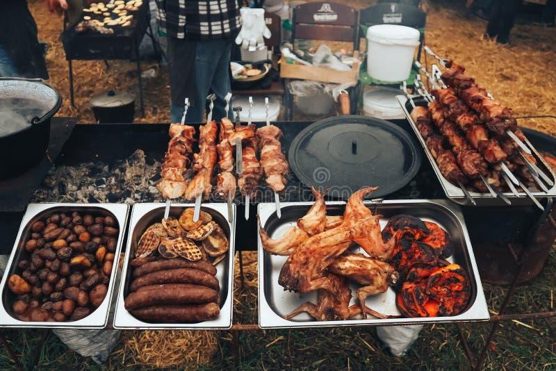 Vlees op de grill met aardappels wordt gebakken die Vleesdelicatessen Festival van straatvoedsel en vlees stock foto