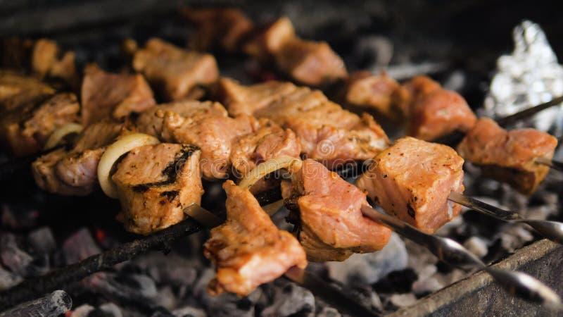 Vlees op vleespen die op steenkolen wordt geroosterd stock afbeeldingen
