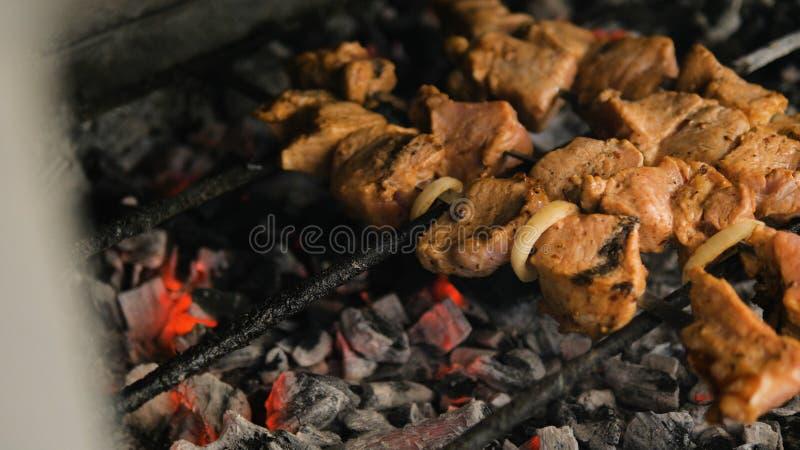 Vlees op vleespen die op steenkolen wordt geroosterd stock afbeelding