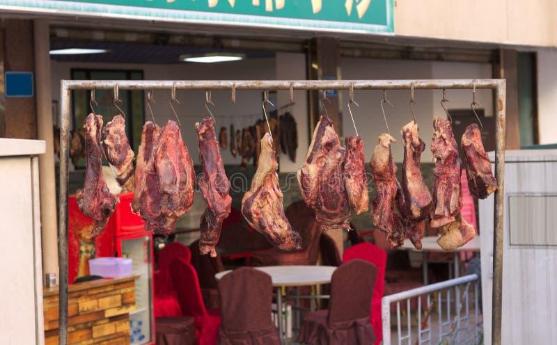 Vlees voor slachting het hangen op de straat stock afbeelding