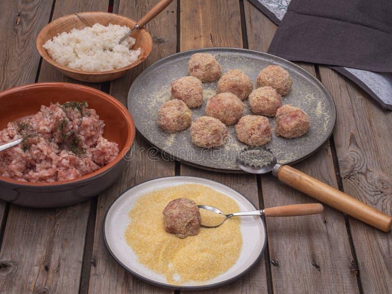Vleesballetjes klaar voor het braden en producten voor hun vervaardiging op ceramische platen, geschoten close-up stock afbeeldingen