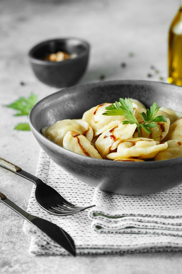 Vleesbollen - Russische pelmeni, ravioli met vlees op een grijze kom stock fotografie