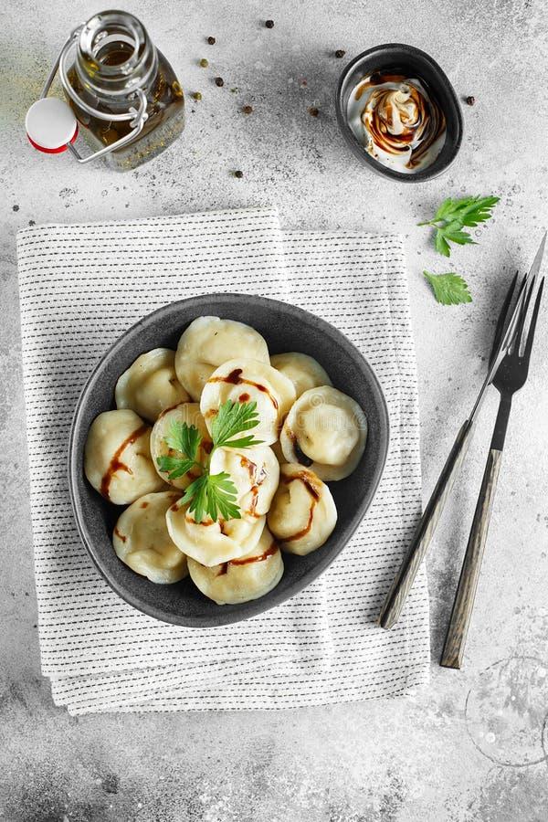 Vleesbollen - Russische pelmeni, ravioli met vlees op een grijze kom Vlak leg samenstelling stock foto