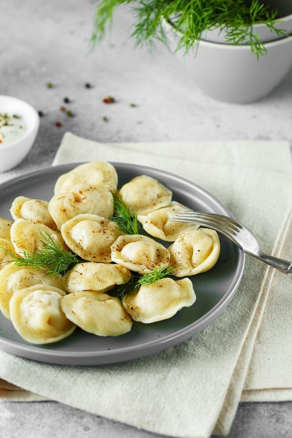Vleesbollen - Russische pelmeni, ravioli met vlees op een grijze plaat royalty-vrije stock foto's