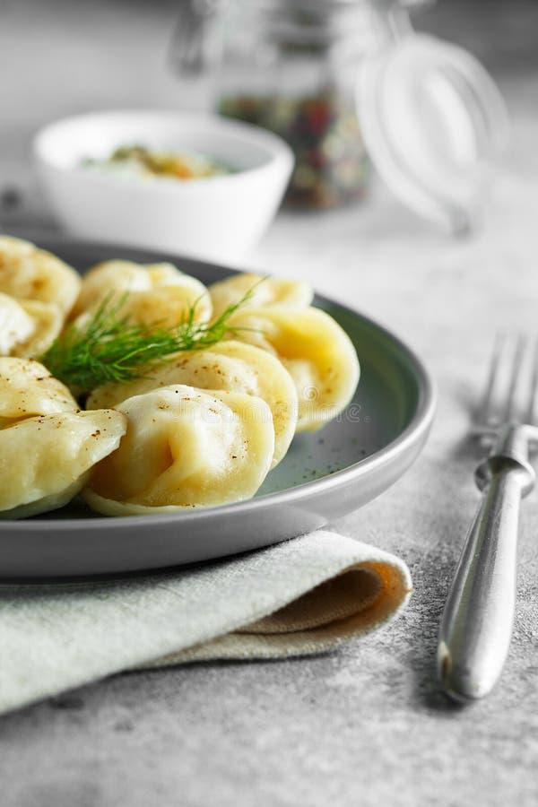 Vleesbollen - Russische pelmeni, ravioli met vlees op een grijze plaat royalty-vrije stock afbeelding