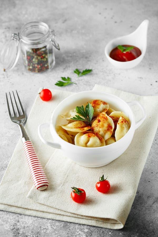 Vleesbollen - Russische pelmeni, ravioli met vlees op een witte kom stock foto's