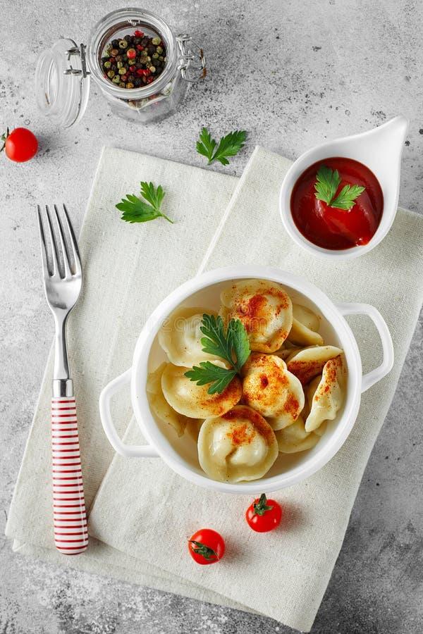 Vleesbollen - Russische pelmeni, ravioli met vlees op een witte kom Vlak leg samenstelling royalty-vrije stock afbeeldingen