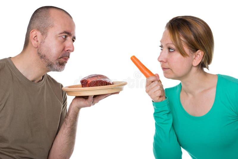 Vleeseter tegenover vegetariër stock afbeeldingen