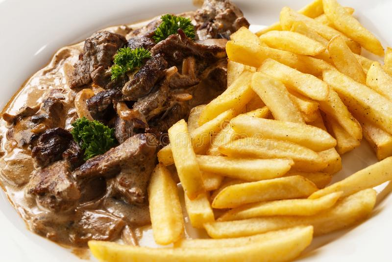 Vleesgoelasj en gebraden aardappels in een plaat op een ge?soleerde witte close-up als achtergrond stock foto