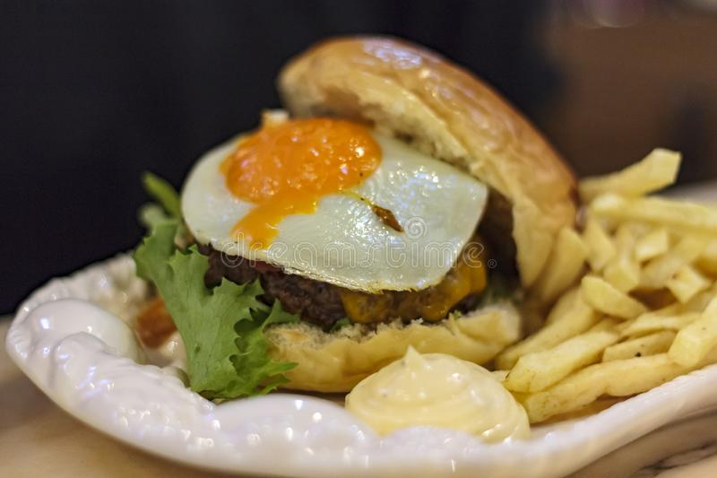 Vleeshamburger met Ei en frieten met saus op een plaat royalty-vrije stock foto