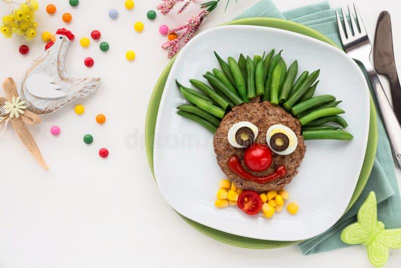Vleeshamburger voor kinderen als leuke glimlachende clown royalty-vrije stock afbeeldingen