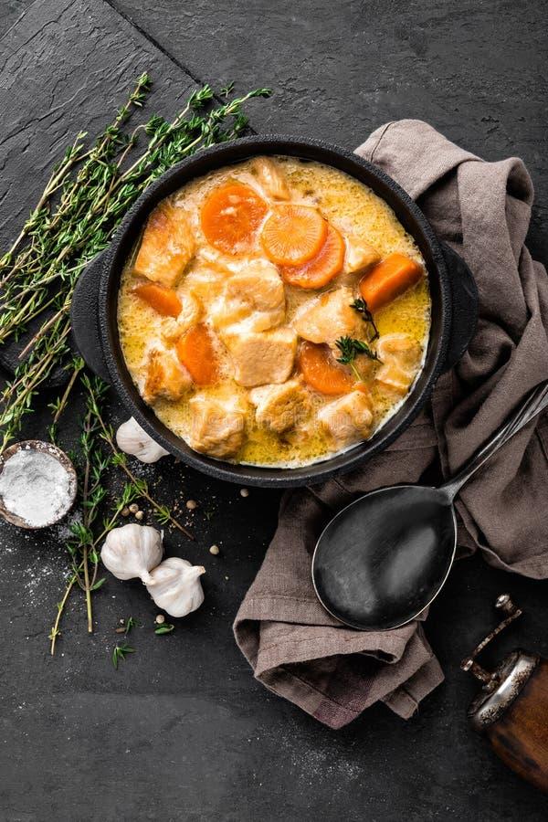 Vleeshutspot, kippenfilet in saus met wortel in een gietijzerpot royalty-vrije stock afbeelding