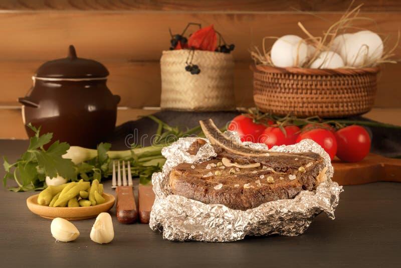 Vleeslapje vlees in folie met verse kruiden en groenten op een houten lijst wordt gebakken die stock foto's