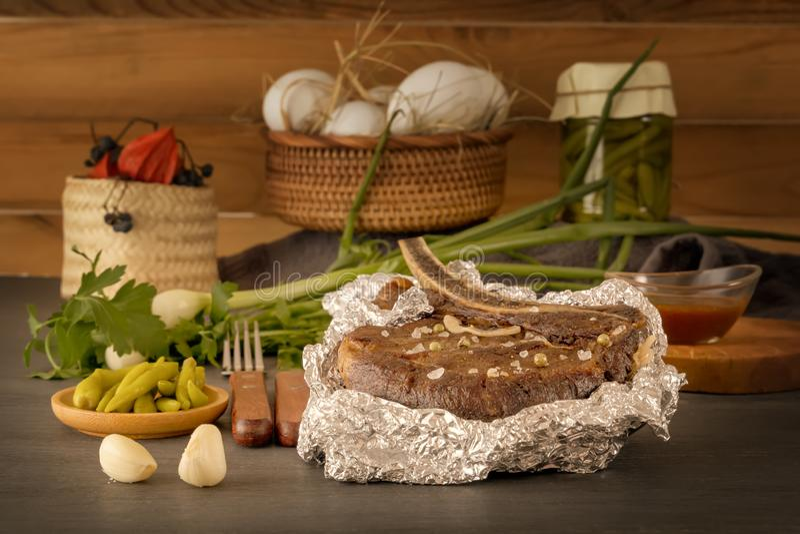 Vleeslapje vlees in folie met verse kruiden en groenten op een houten lijst wordt gebakken die stock afbeeldingen