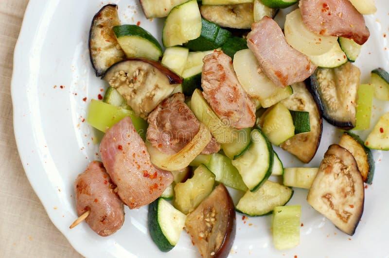 Vleespen met geroosterd kalkoense henvlees met ui, courgette en aubergine op witte plaat royalty-vrije stock foto