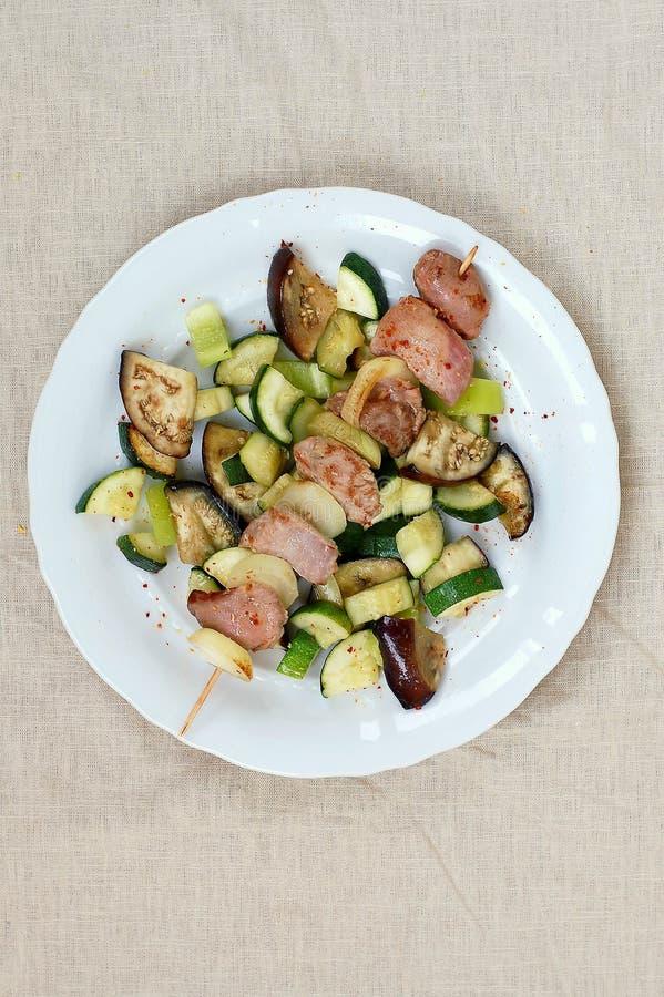 Vleespen met geroosterd kalkoense henvlees met ui, courgette en aubergine op witte plaat stock fotografie