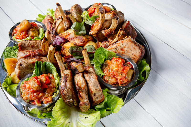 Vleesplaat met heerlijke stukken van vlees, salade, ribben, geroosterde groenten, aardappels en saus op witte houten lijst royalty-vrije stock foto