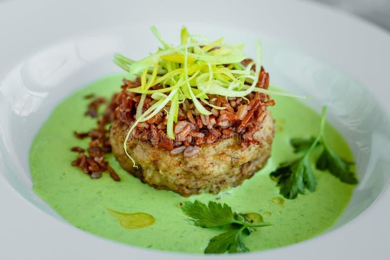 Vleesschotel met rijst, uienplakken, greens en saus stock foto