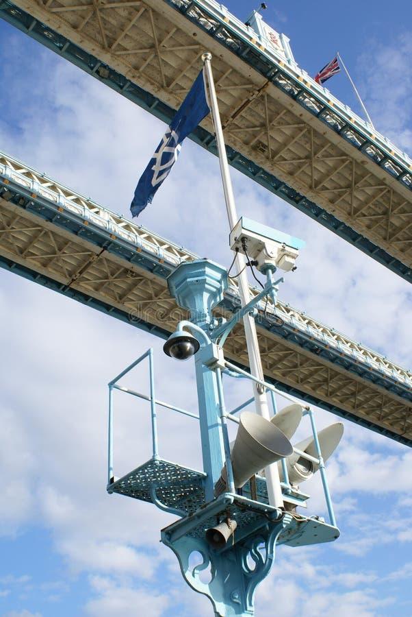 Vleklichten, een openbare luidspreker, vlaggen, & kabeltelevisie-camera op de Torenbrug, Londen, Engeland stock afbeelding