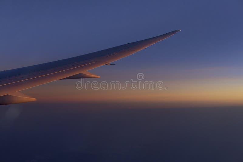 Vleugel die van airplain over de wolken met blauwe hemel vóór zonsondergang vliegen royalty-vrije stock afbeelding