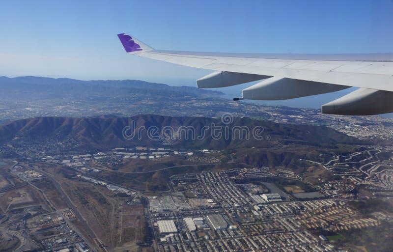 Vleugel die van Hawaiian Airlines-vliegtuig in de lucht boven stad vliegen royalty-vrije stock foto