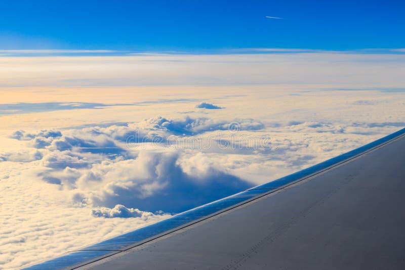 Vleugel die van vliegtuig boven de wolken in de blauwe hemel vliegen stock fotografie