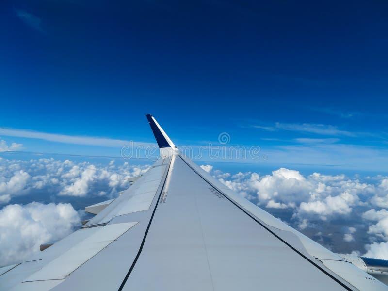 Vleugel van een vliegtuig boven de wolken stock afbeeldingen