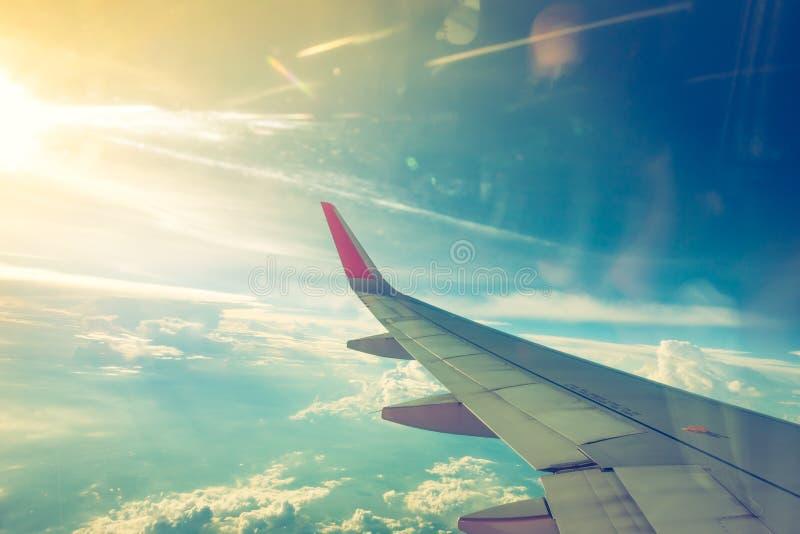 Vleugel van een vliegtuig dat boven de wolken vliegt (Gefiltreerd beeld PR stock afbeeldingen